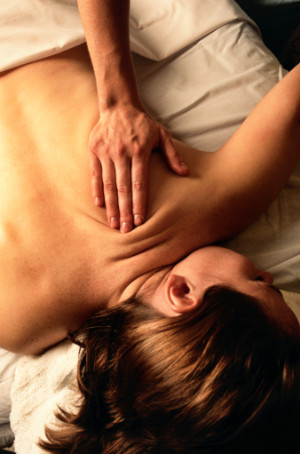 A massage therapist's hand on the back of a client to sooth the muscles during a massage, Charleston SC.