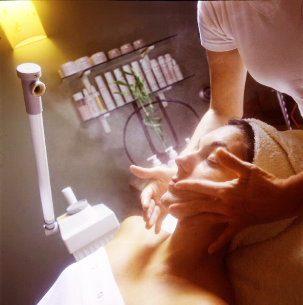 An estetician's hands massage the face during a facial, Charleston SC.